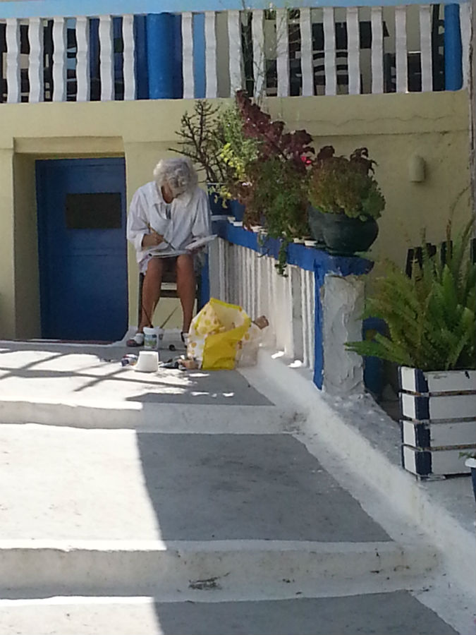 cursist aan het schilderen in Grieks dorpje